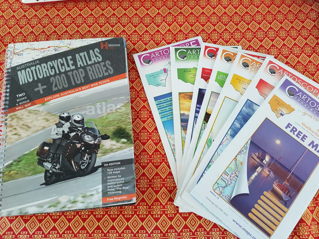 Motorcycle atlas and a pile of cartoscope maps